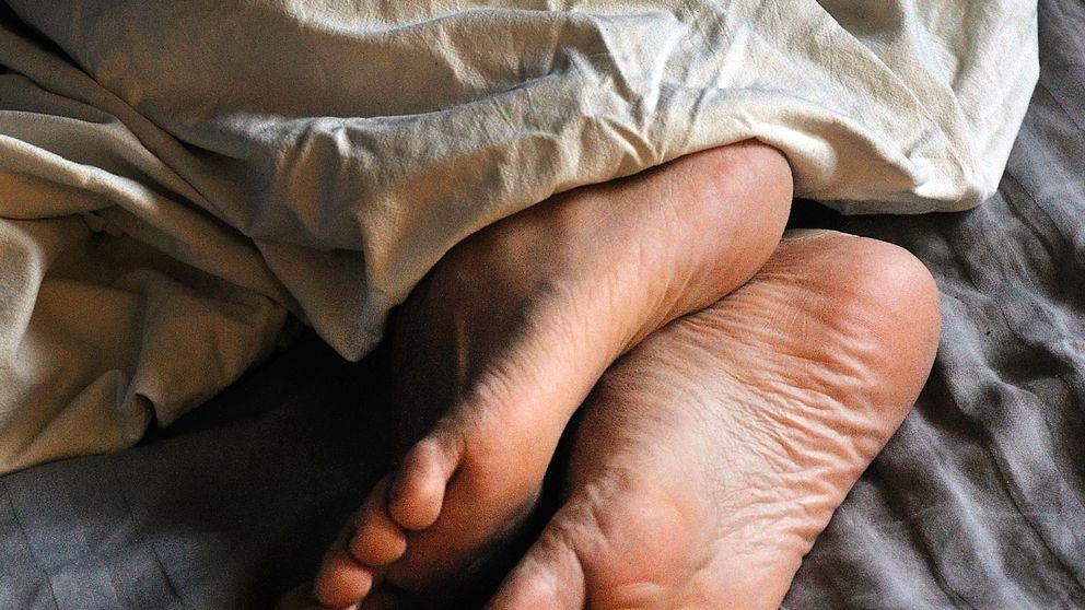 Fötter på person som ligger under täcke