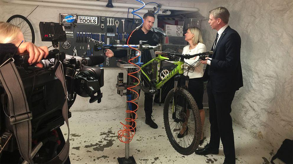 Ministrarna Per Bolund (MP) och Magdalena Andersson (S) i en cykelverkstad. Regeringen vill göra det billigare att få reparationer utförda.