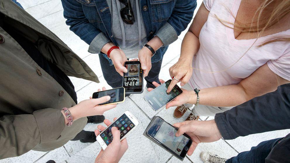 Flera personer med mobiltelefoner, olika märken.