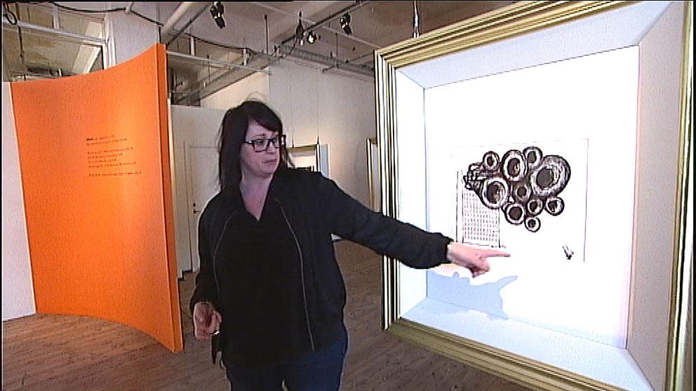 Carina Milde, intendent Ewk-museet, pekar på bild