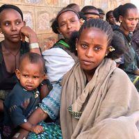 Sittande kvinnor och barn i skugga.