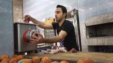 Azad, som strider mot IS i Syrien, maler kött i sin restaurang i den syriska staden Kobane.