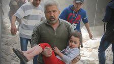 En man bär en skadad flicka efter ett bombangrepp mot Aleppo.
