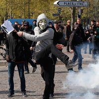 En maskerad demonstrant sparkar till en tårgasbehållare.