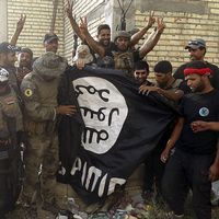 Terrorforskaren Magnus Ranstorp samt män ur irakiska säkerhetstyrkor håller upp en IS-flagga som de rivit ner vid universitetet i Anbar.