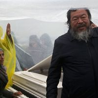 Ai Weiwei håller upp en presenning så att den syriska pianisten Nour al Khzam ska kunna spela i flyktinglägret Idomeni.