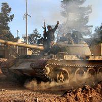 En soldat i den syriska regimens armé ovanpå en stridsvagn i utkanten av Raqqa, 2016.