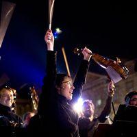 Musiker höjer sina instrument i luften vid en protest mot en ny kontroversiell lag som ska röstas igenom i Frankrikes parlament i dag.