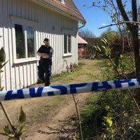 Polis utanför huset. Polisband som spärrar av.