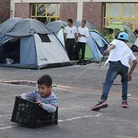 Två barn leker i ett läger för flyktingar i hamnstaden Piraeus utanför Aten.