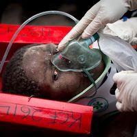 Räddad kvinna bärs ut från raserat hus i Kenya.