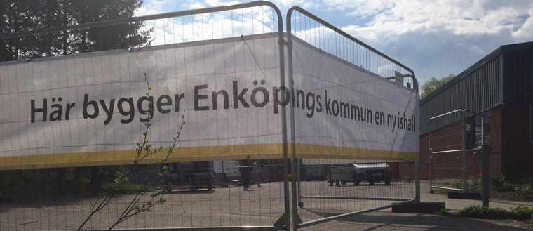 """Banderoll med texten """"Här bygger Enköpings kommun en ny ishall""""."""