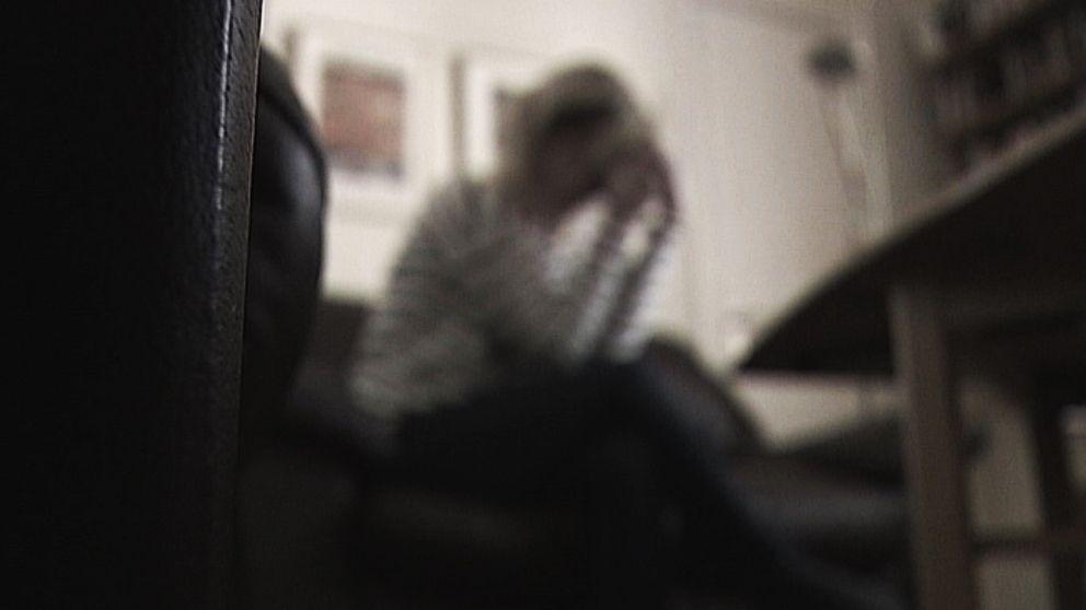 På bilden ser man suddigt en kvinna som sitter på ett golv och håller sig för ansiktet.