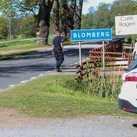 Bild av polis som går med ryggen till vid en skylt med ortsnamnet Blomberg på.