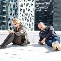 Kvinna och man sitter bredvid varandra och tittar på varsin mobiltelefon.