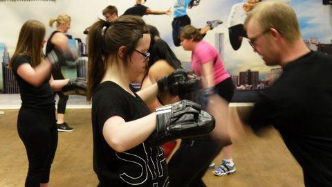 Närbild på två personer som tränar boxning i en gymnastikhall. Flera andra personer som också tränar i bakgrunden.