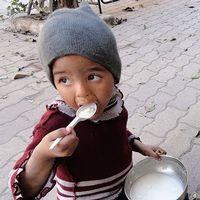 Två barn äter mat som delats ut till dem i flyktinglägret i Yarmouk, Damsaskus.