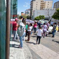 Människor utanför en stängd shoppinggalleria i Caracas.