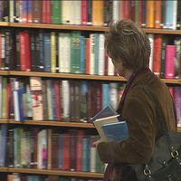 Kvinna med tre böcker under armen. Från rotundan i stadsbiblioteket.