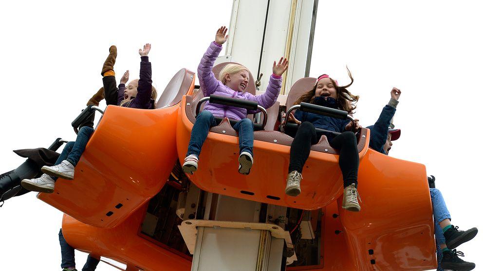 Barn som håller upp händerna när de åker en attraktion på Gröna Lund.