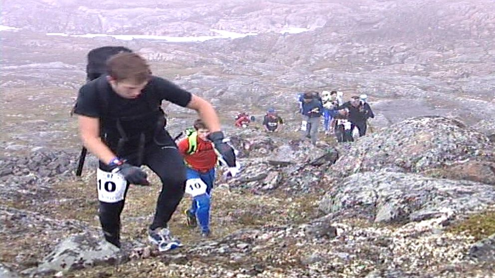 tävlande i ett fjällmaraton tar sig uppför en klippig brant