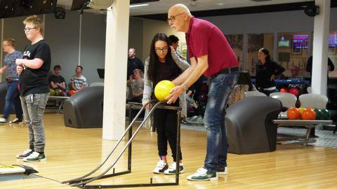 Interör från bowlinghall med två personer i fokus, på väg att rulla iväg ett klot med hjälp av en stålställning.