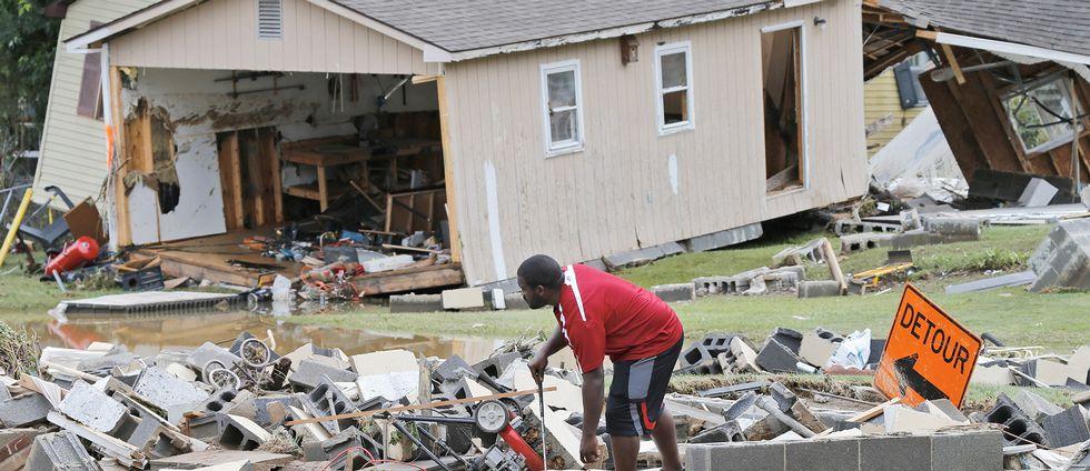 En man i White Sulphur Springs, i West Virginia, röjer upp efter förstörelsen i översvämningarnas spår.