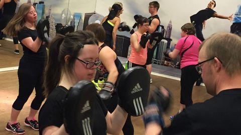 Flera personer i en gymnastikhall tränar boxning med handskar och mitsar.