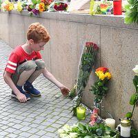 En pojke som lägger blommor vid platsen där många dog.