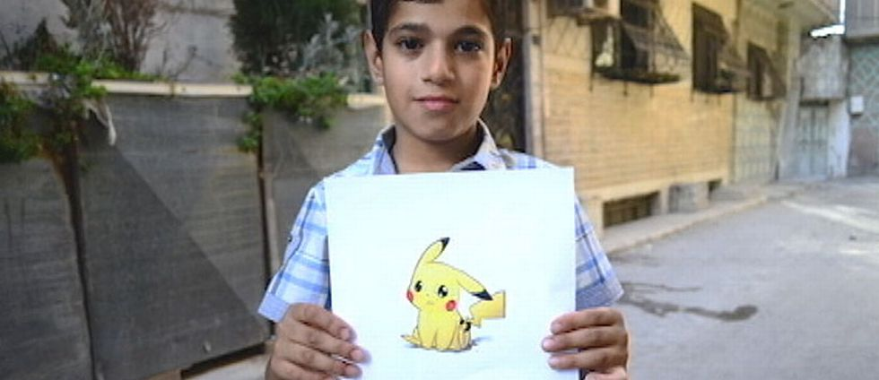 Syriska barn håller upp fotografier på figurer från Pokémon för att påminna om situationen i det krigshärjade Syrien.