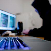 En man iklädd huvtröja sitter framför en dator.