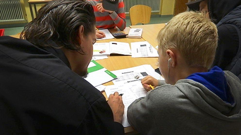 Här får en grundskoleelev hjälp med läxorna.
