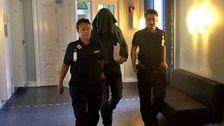 En av de misstänkta förs in i rättegångssalen