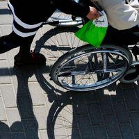 En person skjutsar en annan i rullstol, inga ansikten syns.