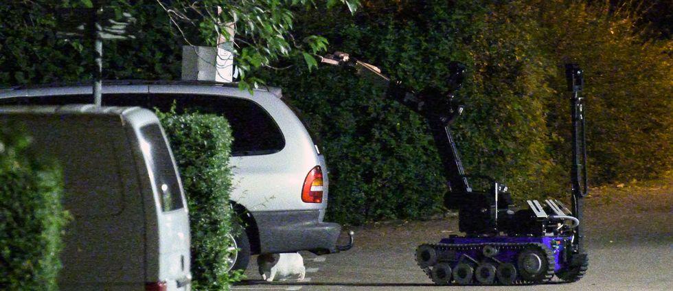 En vit katt tar skydd medan polisens bombrobot lyfter bort det misstänkta föremålet