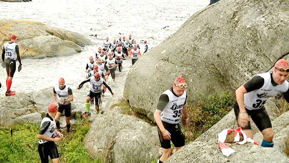 Deltagarna tar sig upp ur havet och springer på klippor.