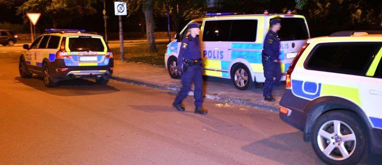 Två poliser och tre polisbilar.