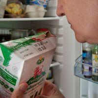 En kvinna luktar på innehållet i ett mjölkpaket.