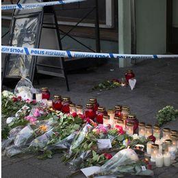 Sveriges rikes lag (vänster) samt blommor och ljus vid platsen för dödsskjutningarna på Vårväderstorget på Hisingen i Göteborg. Arkivbild.