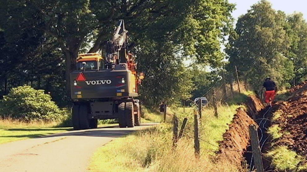 En grävmaskin på en grusväg intill ett uppgrävt dike.