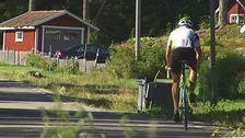 Man i lycra som cyklar på liten byväg.
