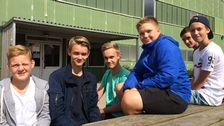 en grupp pojkar sitter på en bänk framför en skola