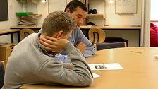 Manlig lärare med blå tröja och mörkt hår sitter vid ett bord med elev med kort hår och grå tröja och tittar på ett papper.