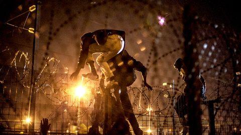 Flyktingar som klättrar över stängsel vid Eurotunneln.