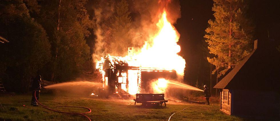 Två brandmän sprutar vatten på hus