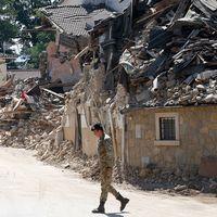 En italiensk soldat går förbi hus som står i ruiner i Villa San Lorenzo, nära byn Amatrice.