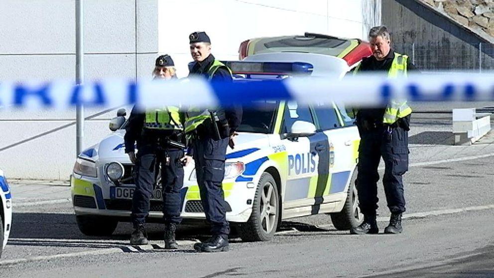 Poliser bakom avspärrningar.