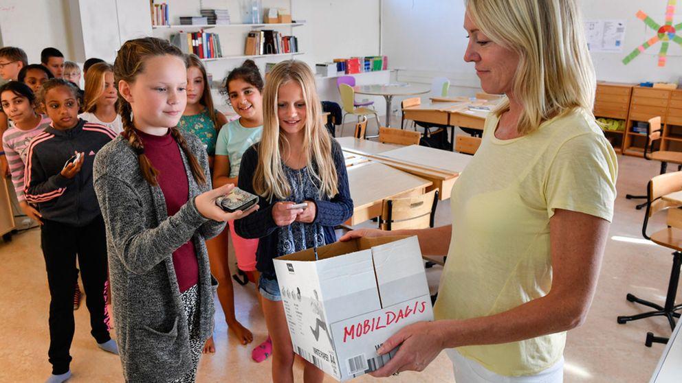 """Catharina Rapp, lärare för en femteklass på Igelboda skola i Nacka, samlar in mobilerna i """"mobildagiset"""" innan skoldagen startar."""