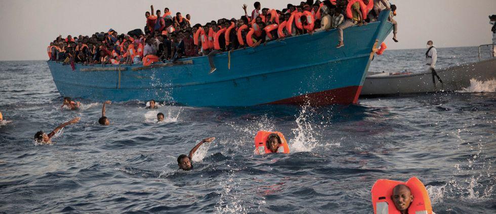 Människor i flytvästar hoppar från en båt i Medelhavet och simmar mot en räddningsbåt under måndagen.