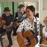 Glada musikanter spelar för äldre.